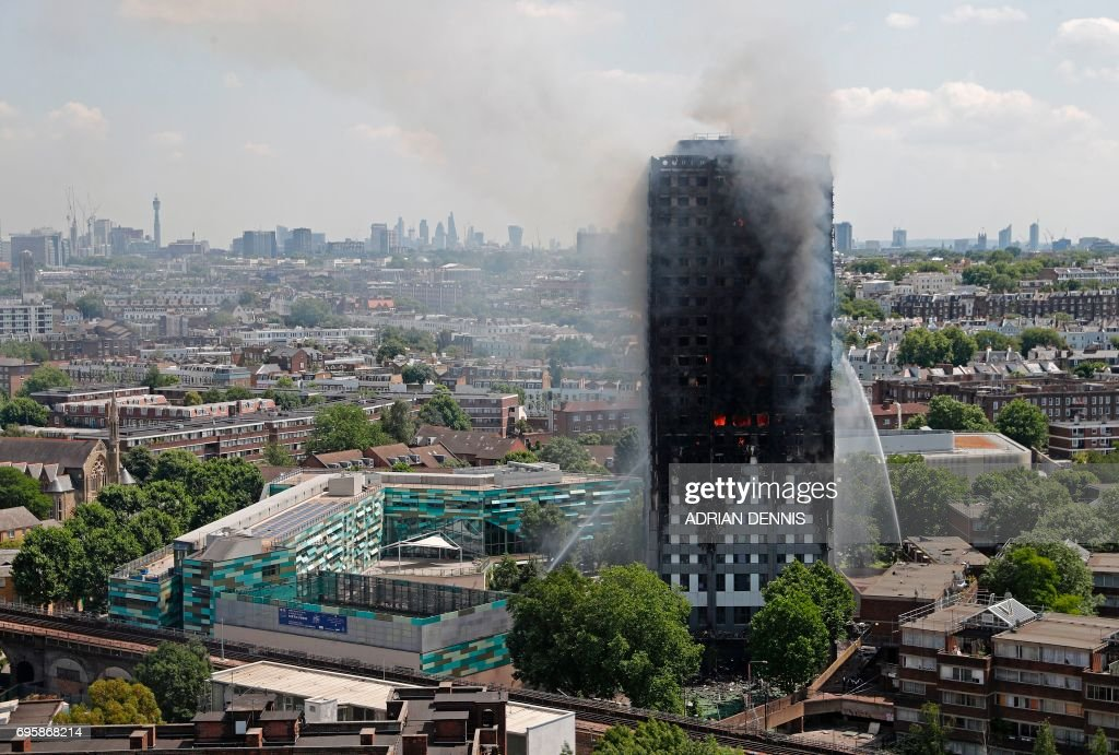 TOPSHOT - Smoke and flames billows from Grenfell Tower as firefighters attempt to control a blaze at a residential block of flats on June 14, 2017 in west London. At least six people were killed Wednesday when a massive fire tore through a London apartment block in the middle of the night, with witnesses reporting terrified people had leapt from the 24-storey tower. / AFP PHOTO / Adrian DENNIS