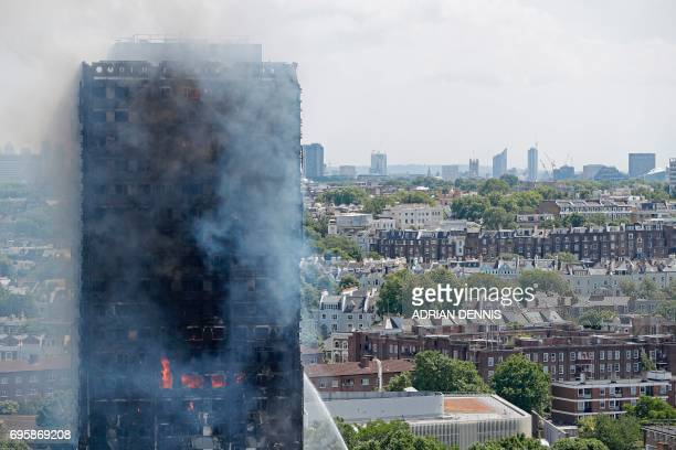 Smoke and flames billows from Grenfell Tower as firefighters attempt to control a blaze at a residential block of flats on June 14 2017 in west...