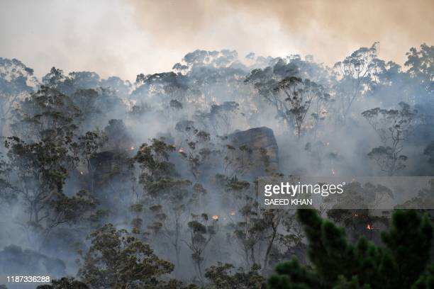 TOPSHOT Smoke and flames from a back burn conducted to secure residential areas from encroaching bushfires are seen at the Spencer area in Central...