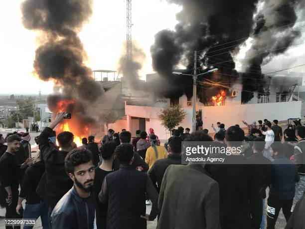 Smoke and flames rise after protesters set fire to some political party buildings and government offices in Seyitsadik district during protests due...