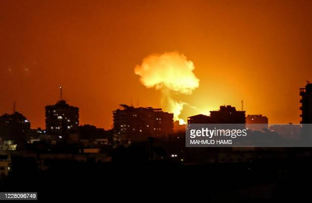 Smoke and flames rise after war planes belonging to the Israeli army carried out airstrikes over Gaza City on August 18, 2020. - A rocket was fired...