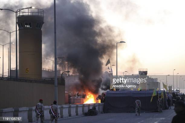 Smoke and flames rise as outraged Iraqi protesters storm the US Embassy in Baghdad protesting Washington's attacks on armed battalions belong to...