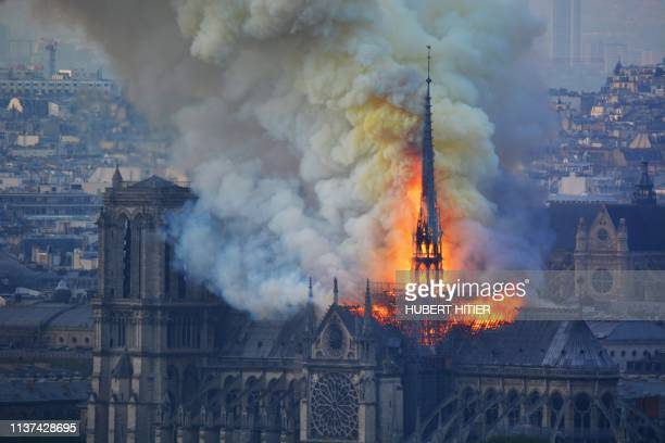 TOPSHOT Smoke and flames rise during a fire at the landmark NotreDame Cathedral in central Paris on April 15 potentially involving renovation works...