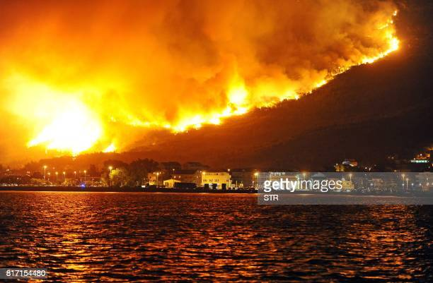 TOPSHOT Smoke and flames rise from a fire in the village of Podstrana near the Adriatic coastal town of Split on July 18 2017 Montenegro asked on...