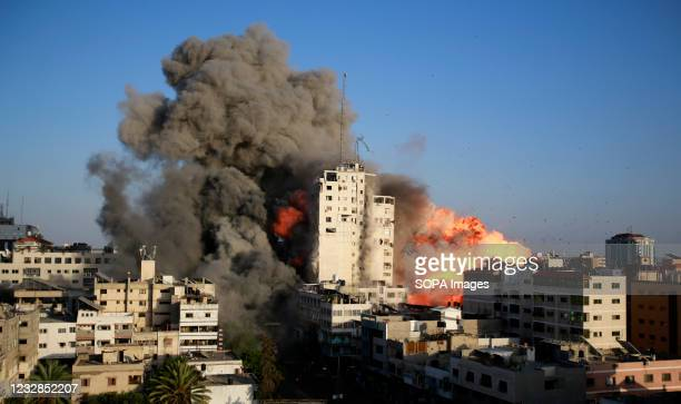 Smoke and flames rise from a tower building destroyed by Israeli air strikes amid a flare-up of Israeli-Palestinian violence in Gaza City Israel...
