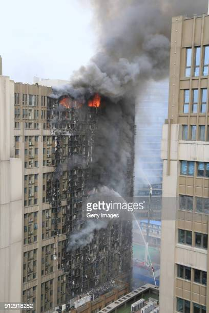 Smoke and flames rise from an apartment building on February 1, 2018 in Zhengzhou, China. The fire broke out at around 1:40 p.m., and there are no...
