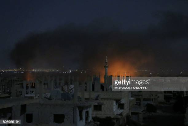 TOPSHOT Smoke and flames rise from buildings following a reported government strike on a rebelheld area in Syria's southern city of Daraa late on...