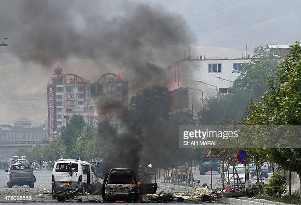 Smoke and flames rise from burning vehicles at the site of an attack in front of the Afghan Parliament building in Kabul on June 22 2015 Taliban...