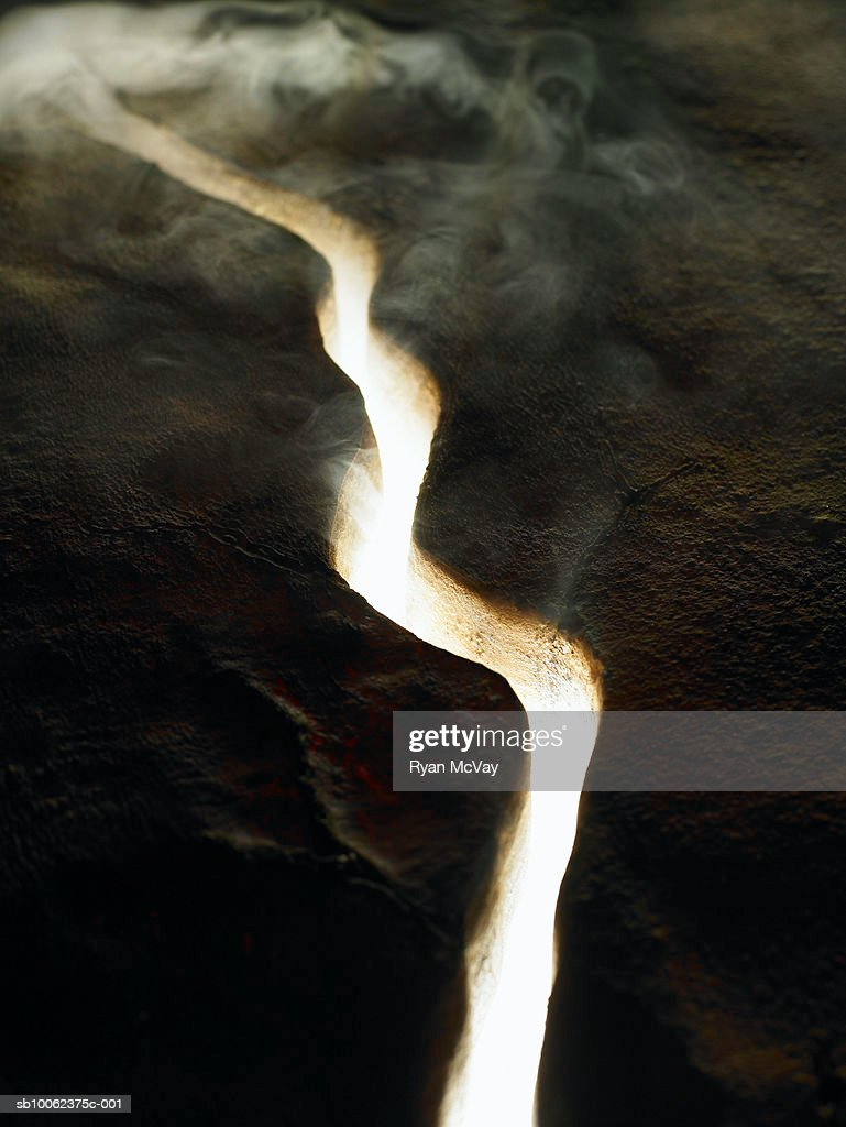 Smoke and light coming through crack in lava rock, elevated view : Stock Photo