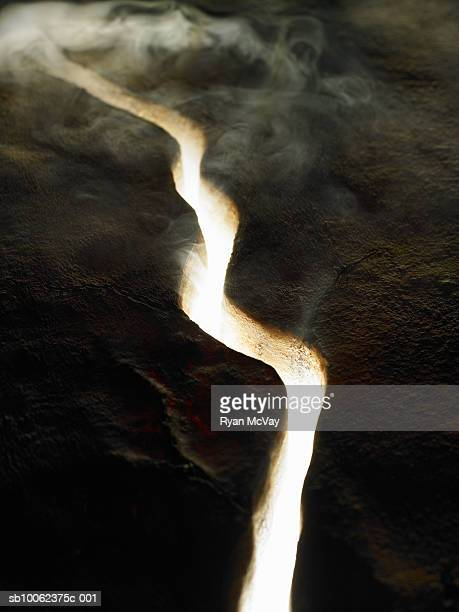 Smoke and light coming through crack in lava rock, elevated view