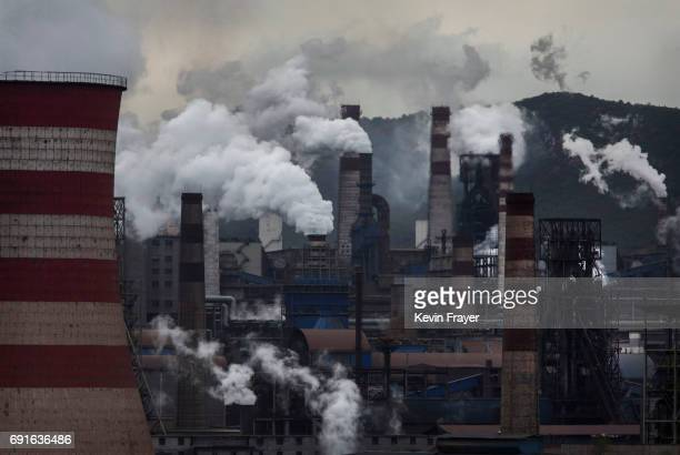 Smoke and steam billows from a Chinese state owned steel plant on June 2 2017 in Hebei China China the world's largest polluter reaffirmed its...