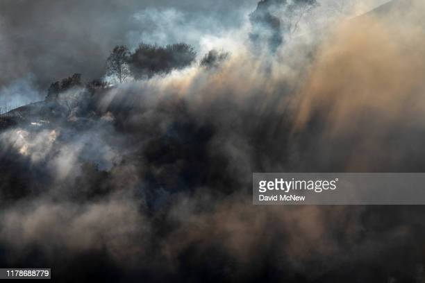 Smoke and steam from water dropped from a firefighting helicopter rise from the Getty Fire on October 28 2019 in Los Angeles California Reported at...