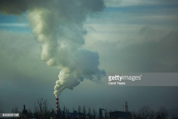 smoke billowing from industrial plan - carbon dioxide stock pictures, royalty-free photos & images