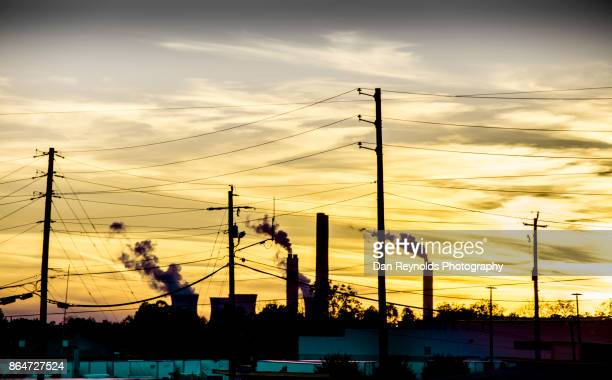 Smoke billowing from Industrial Plant against Sunset