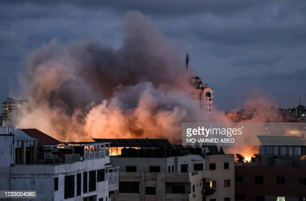 Smoke billows above buildings during an Israeli air strike on Gaza City, on May 20, 2021. - Israel and the Palestinians are mired in their worst...