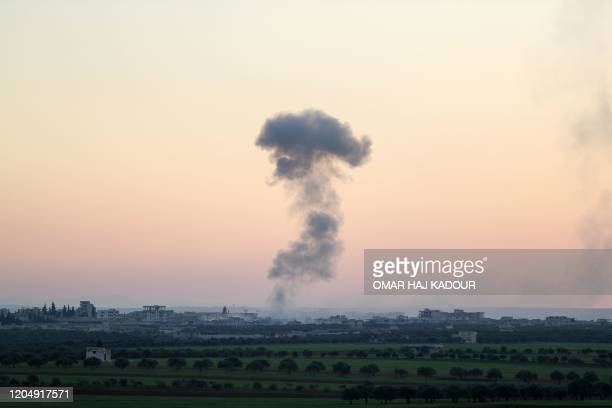 Smoke billows above the rebel-controlled village of Sarmin near the regime-held town of Saraqeb, in the eastern part of the Idlib province in...