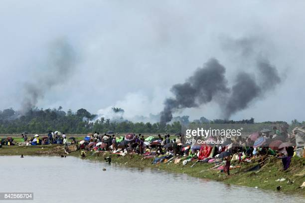 Smoke billows above what is believed to be a burning village in Myanmar's Rakhine state as members of the Rohingya Muslim minority take shelter in a...