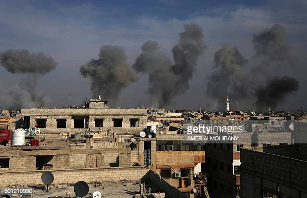 TOPSHOT Smoke billows after air strikes by regime forces on the town of Douma in the eastern Ghouta region a rebel stronghold east of the capital...