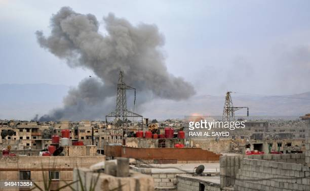 Smoke billows and an explosion erupts in a southern district of the Syrian capital Damascus during regime strikes targeting the Islamic State group...