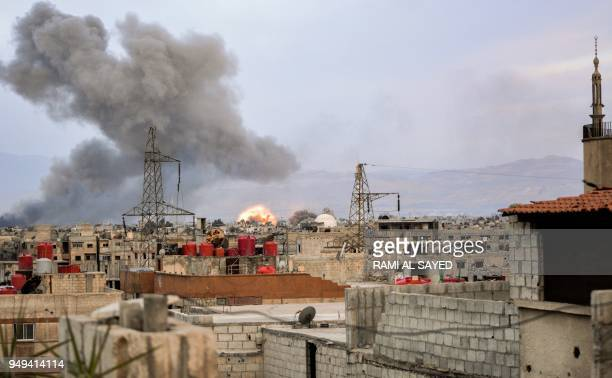 TOPSHOT Smoke billows and an explosion erupts in a southern district of the Syrian capital Damascus during regime strikes targeting the Islamic State...