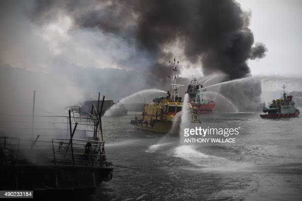 Smoke billows as firefighters extinguish fires on boats at the Shau Kei Wan typhoon shelter in Hong Kong on September 27 2015 Explosions were heard...