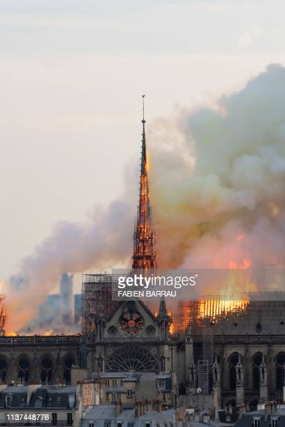 Smoke billows as flames burn through the roof of the NotreDame de Paris Cathedral on April 15 in the French capital Paris A huge fire swept through...