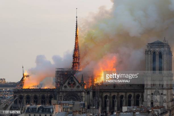 Smoke billows as flames burn through the roof of the Notre-Dame de Paris Cathedral on April 15 in the French capital Paris. - A huge fire swept...
