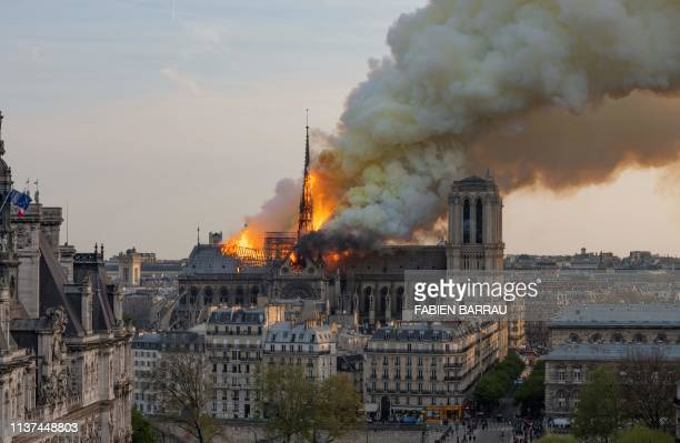 TOPSHOT Smoke billows as flames burn through the roof of the NotreDame de Paris Cathedral on April 15 in the French capital Paris A huge fire swept...