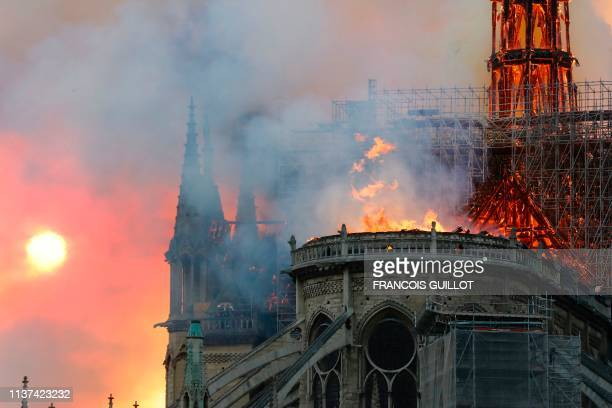 TOPSHOT Smoke billows as flames destroy the roof of the landmark NotreDame Cathedral in central Paris on April 15 2019 A major fire broke out at the...