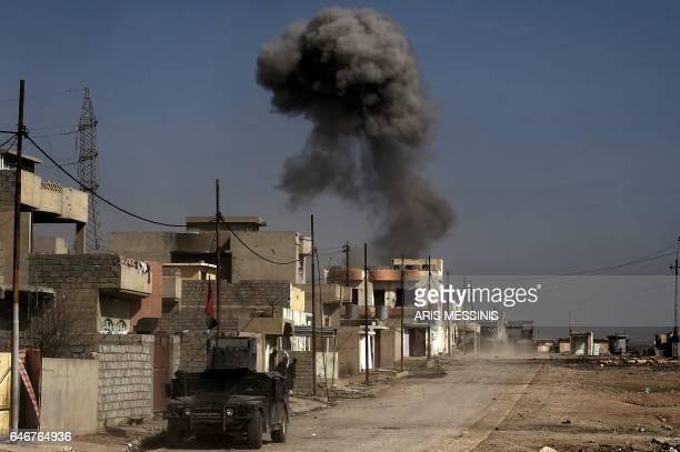 Smoke billows as Iraqi forces hold a position on a street in Mosul on March 1 during an offensive by security forces to retake the western parts of...