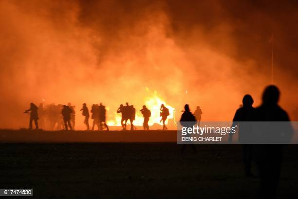TOPSHOT Smoke billows as migrants start a fire during clashes with police at the 'Jungle' migrant camp in Calais northern France on October 23 2016...