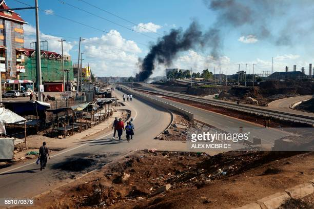 Smoke billows as supporter of Kenya's opposition party National Super Alliance block the road at Mathare slum in Nairobi on November 28 as they...