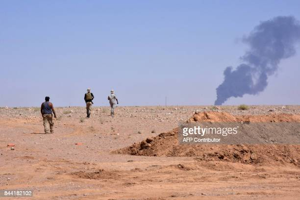 Smoke billows as Syrian government forces advance in AlShula on the southwestern outskirts of Deir Ezzor on September 8 during the ongoing battle...