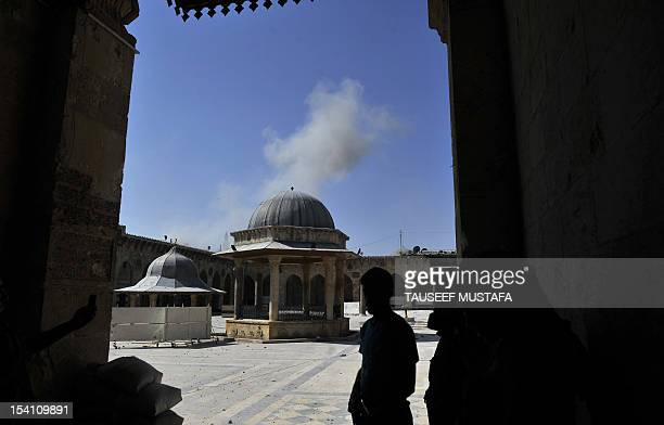 Smoke billows as Syrian rebels take position during clashes with regime forces at the Umayyad Mosque in the old city of Aleppo hours before the...