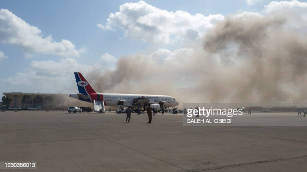 Smoke billows at the Aden Airport on December 30 after explosions rocked the Yemeni airport shortly after the arrival of a plane carrying members of...