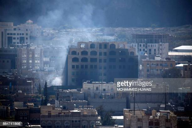 TOPSHOT Smoke billows behind a building in the Yemeni capital Sanaa on December 3 during clashes between Huthi rebels and supporters of Yemeni...