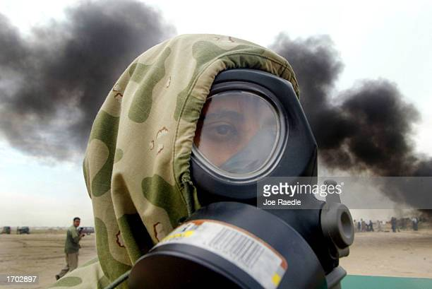 Smoke billows behind a member of the Civil Defense Authority as he participates in a mock chemical attack by wearing a chemical suit and gas mask...