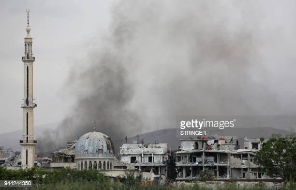 TOPSHOT Smoke billows behind destroyed buildings in the former rebelheld town of Saqba in the Eastern Ghouta region on the outskirts of Damascus on...