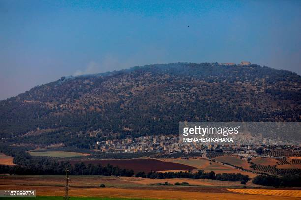 Smoke billows during a forest fire on Mount Tabor in northern Israel's Galilee region on July 26 2019 A forest fire in northern Israel's Galilee...