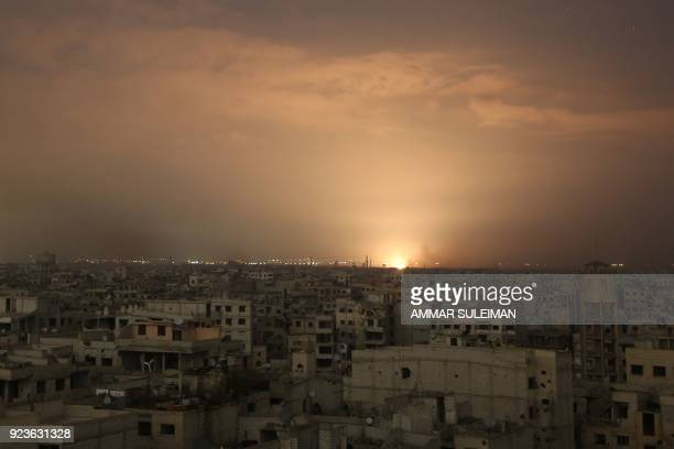 Smoke billows following a regime air strike on the besieged Eastern Ghouta region on the outskirts of the capital Damascus late on February 23 2018...