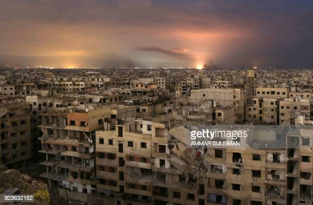 TOPSHOT Smoke billows following a regime air strike on the besieged Eastern Ghouta region on the outskirts of the capital Damascus late on February...