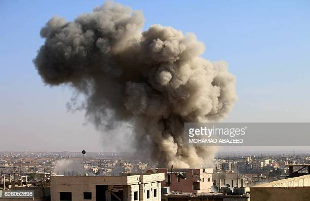 TOPSHOT Smoke billows following a reported air strike by Syrian government forces in a rebelheld area of Daraa in southern Syria on November 27 2016...