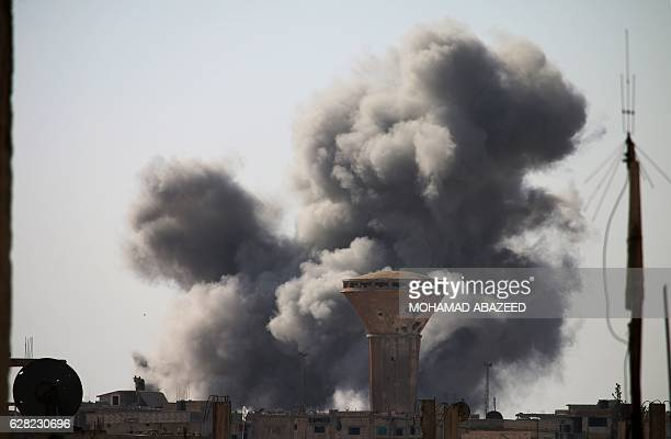 TOPSHOT Smoke billows following a reported air strike by Syrian government forces in a rebelheld area of Daraa in southern Syria on December 7 2016 /...