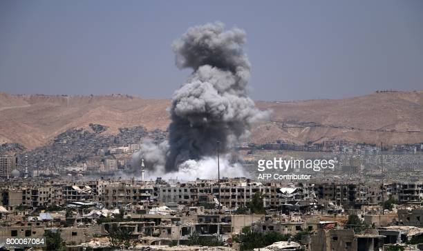 Smoke billows following a reported air strike by Syrian government forces in the rebelheld parts of the Jobar district on the eastern outskirts of...