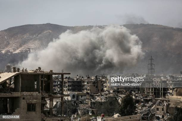 TOPSHOT Smoke billows following a reported air strike in the rebelheld parts of the Jobar district on the eastern outskirts of the Syrian capital...