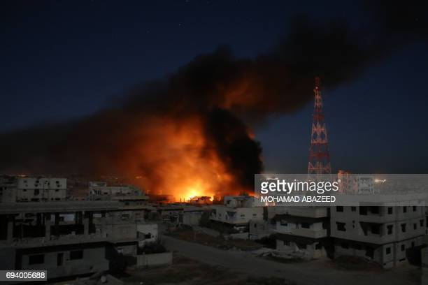 TOPSHOT CORRECTION Smoke billows following a reported air strike on a rebelheld area in the southern Syrian city of Daraa early on June 9 2017 / AFP...