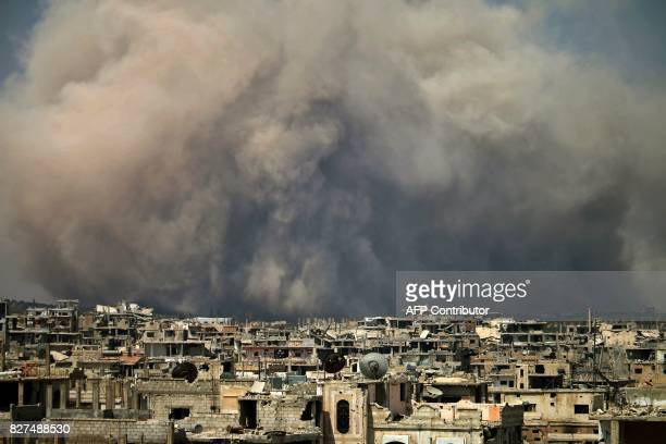 TOPSHOT Smoke billows following a reported air strike on a rebelheld area in the southern Syrian city of Daraa on August 8 2017 / AFP PHOTO / Mohamad...