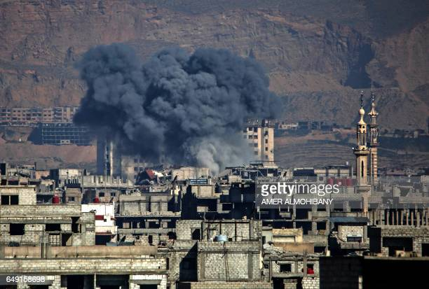 TOPSHOT Smoke billows following an air strike in the Syrian rebelheld town of Arbin in the eastern Ghouta region on the outskirts of the capital...