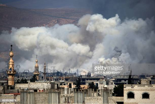 TOPSHOT Smoke billows following reported air strikes by Syrian government forces on Damascus' north eastern rebelheld alQaboun suburb on March 15...