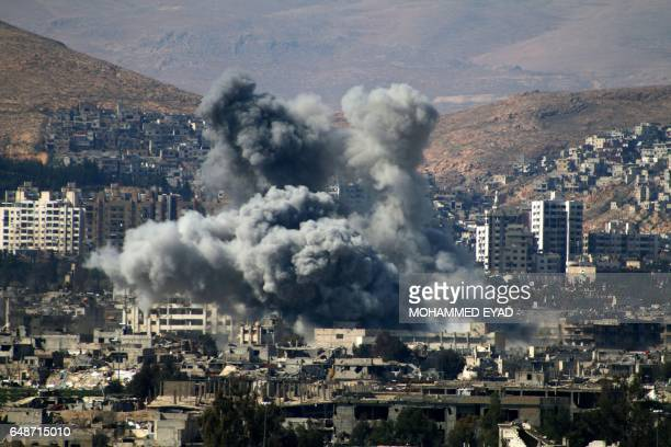 Smoke billows following reported air strikes by Syrian regime forces in the rebelheld area of Qabun east of the capital Damascus on March 6 2017 /...
